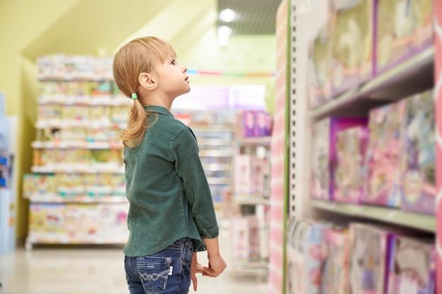 Ragazza divertente che sta nel grande negozio di giocattoli e che esamina i nuovi giocattoli