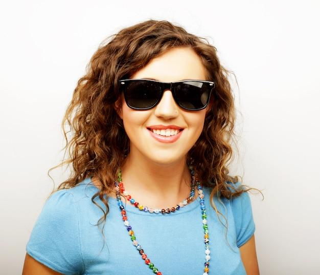 Ragazza divertente in occhiali da sole con espressione di sorpresa su sfondo bianco