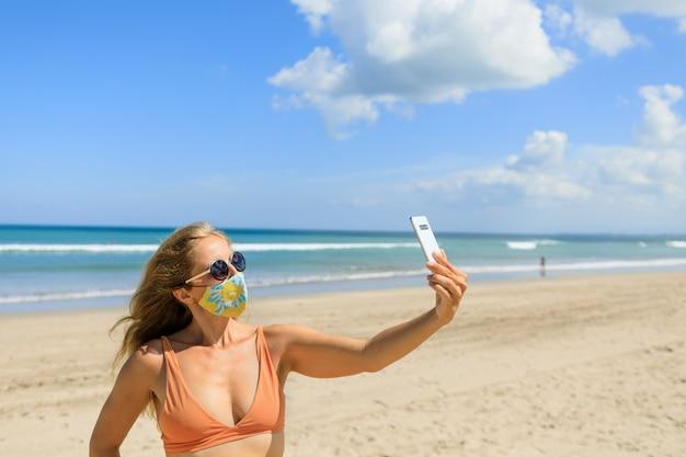 Ragazza divertente che cattura foto selfie tramite smartphone sulla spiaggia del mare tropicale.