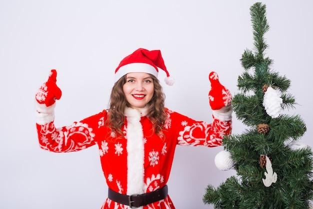 Ragazza divertente in costume da portare della santa di natale vicino all'albero di natale che mostra i pollici aumenta il gesto