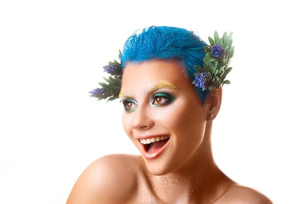 Ragazza divertente con trucco multicolore che sorride sul colpo dello studio isolato sfondo bianco