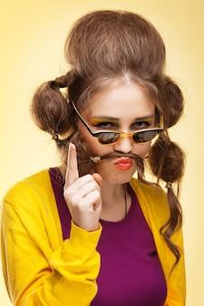 Ragazza divertente con i baffi fatti dei suoi capelli scuotendo il dito alla telecamera