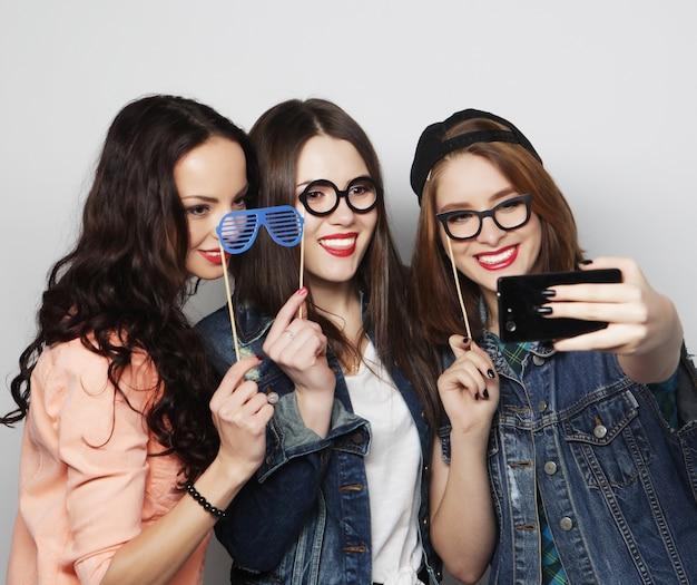 Ragazze divertenti pronte per la festa facendo selfie