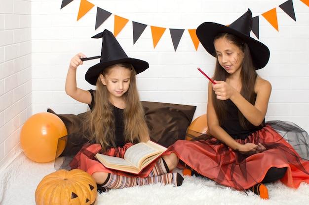 Ragazze divertenti in costumi da strega per halloween spaventano con l'aiuto di un libro magico