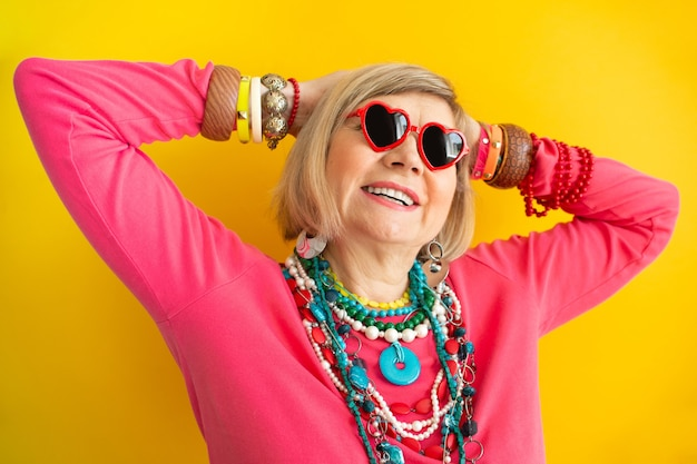 Ritratti divertenti della nonna. anziana anziana che si diverte in abiti eleganti, concetti su persone anziane su sfondo colorato.