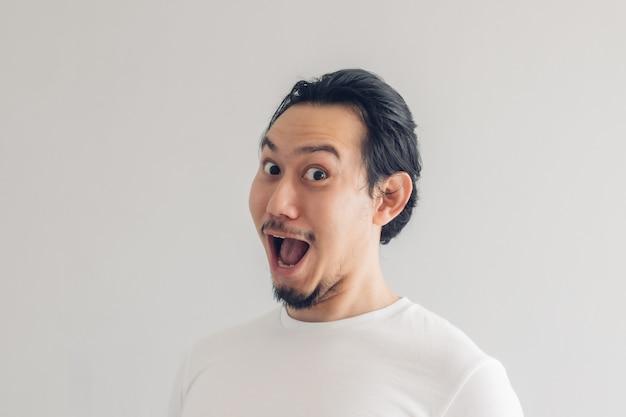 Fronte di sorriso sorridente divertente dell'uomo in maglietta bianca