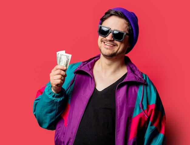 Ragazzo divertente in giacca stile anni '80 e occhiali da sole tenere soldi su backgorund rosso