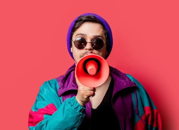 Ragazzo divertente in giacca e occhiali da sole stile anni '80 tiene il megafono su backgorund rosso