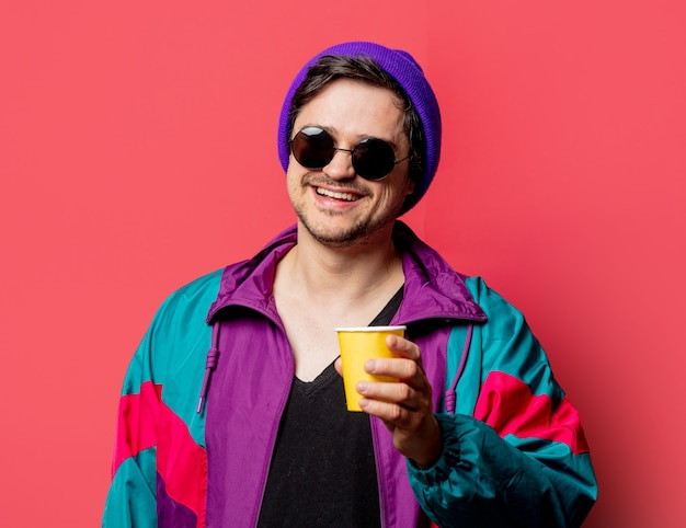 Ragazzo divertente in giacca e occhiali da sole stile anni '80 tiene il bicchiere di carta su backgorund rosso