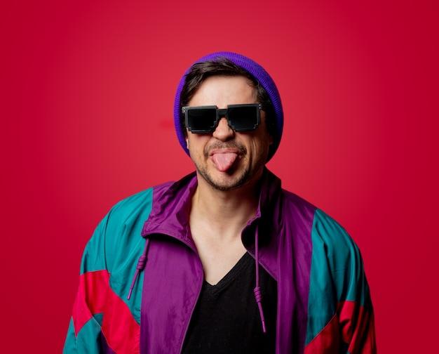 Ragazzo divertente in giacca stile anni '80 e occhiali da sole su backgorund rosso