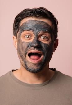 Ragazzo divertente con una maschera cosmetica sul viso in rosa