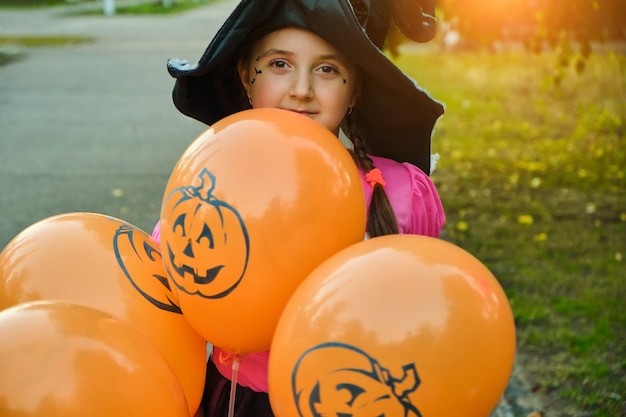 Ragazza divertente del bambino di halloween con il trucco sul viso in costumi di carnevale all'aperto.