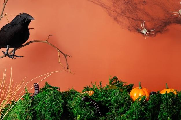 Scenario divertente di halloween il corvo nero si siede sul muschio verde del ramo di un albero da cui escono i vermi gelatinosi