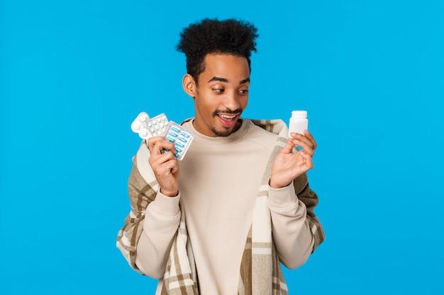 Divertente bell'uomo africano che sceglie quale pillola prendere per primo perché si è ammalato, stare a casa con il raffreddore o l'influenza, tenendo le pillole dalla farmacia, usare le medicine per migliorare, prendersi cura della salute, parete blu