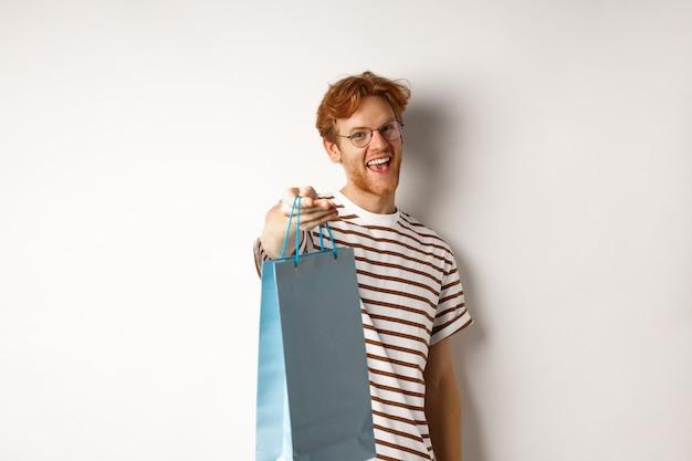 Divertente bel ragazzo che dà la borsa della spesa con un regalo, congratulazioni con san valentino e sorridente, in piedi su sfondo bianco.