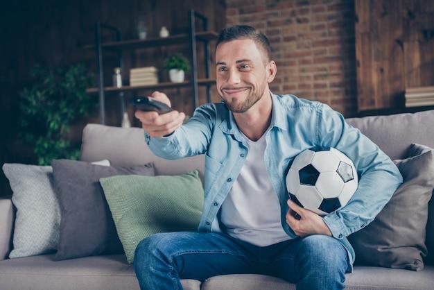 Divertente bel ragazzo guarda il calcio tenere palla telecomando