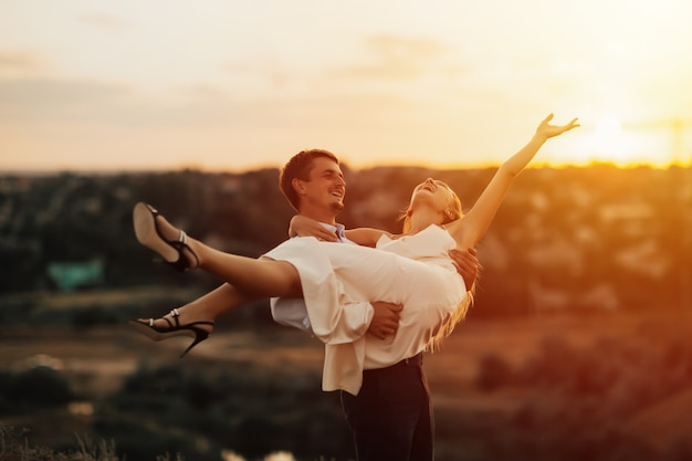 Coppie felici divertenti divertendosi all'aperto. guy ha sollevato il suo amante tra le braccia, la ragazza ride.