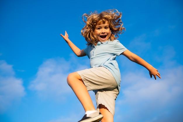 Un ragazzino divertente e felice che si diverte al parco sul cielo azzurro il bambino si gode il concetto di infanzia della natura