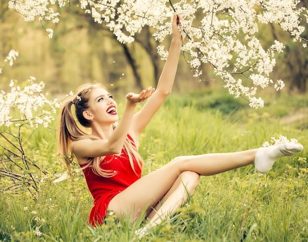 Giovane donna felice divertente che gode della bellezza in un giardino fiorito di primavera bella donna vicino all'albero in fiore bellezza e moda di caratteristica stagionale