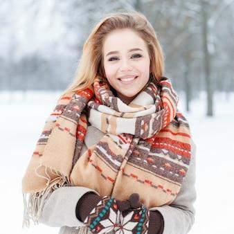 Giovane donna felice divertente con un bel sorriso in vestiti alla moda di inverno su un alberi innevati nel parco. il divertimento della ragazza carina trascorre del tempo all'aperto.