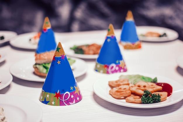 Cappelli divertenti e una varietà di piatti in tavola per una festa per bambini
