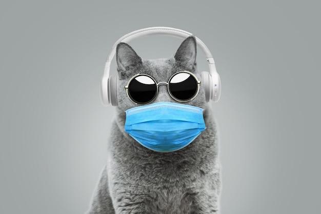 Gatto divertente hipster con occhiali da sole in una maschera medica ascolta musica con cuffie bianche. concetto di pandemia e coronavirus. idea creativa di protezione antivirus