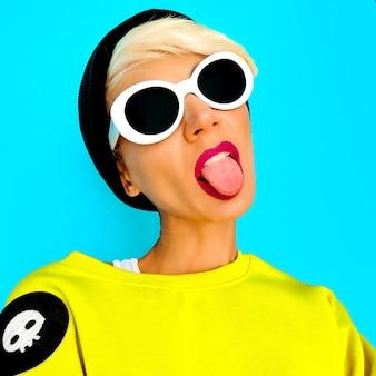 Funny hipster tom boy girl in accessori alla moda beanie e occhiali. look alla moda urbana
