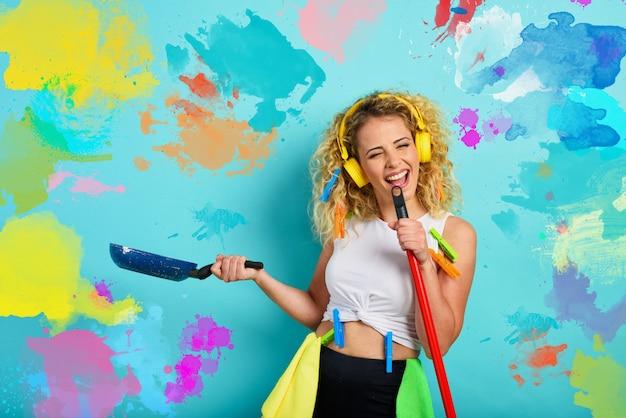 La casalinga divertente usa la scopa come un microfono rock