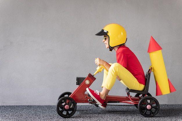 Bambino divertente che guida un'auto da corsa