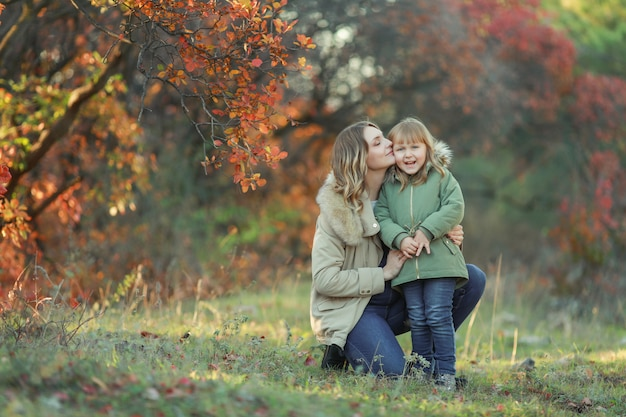 Ragazza divertente del bambino che finge di posare nella foresta di autunno, indossando un cappotto verde