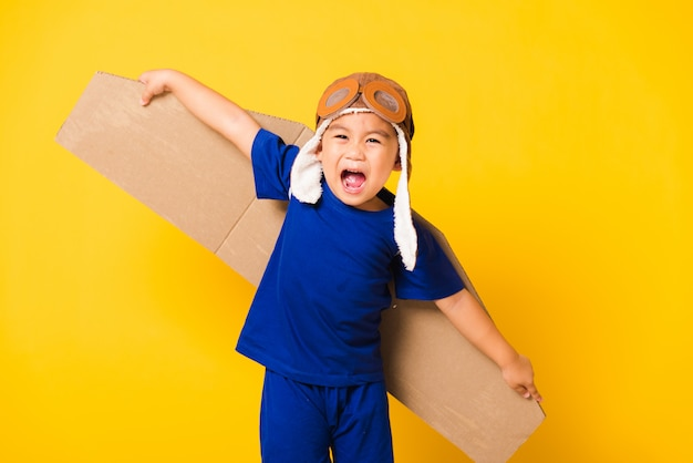 Il sorriso del bambino divertente indossa il cappello da pilota che gioca e gli occhiali di protezione con le ali dell'aeroplano del cartone del giocattolo che volano