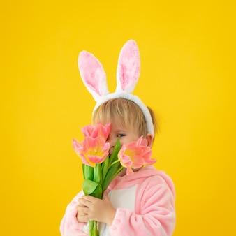 Bambino divertente che indossa le orecchie del coniglietto di pasqua e che tiene un mazzo di tulipani contro il muro giallo.
