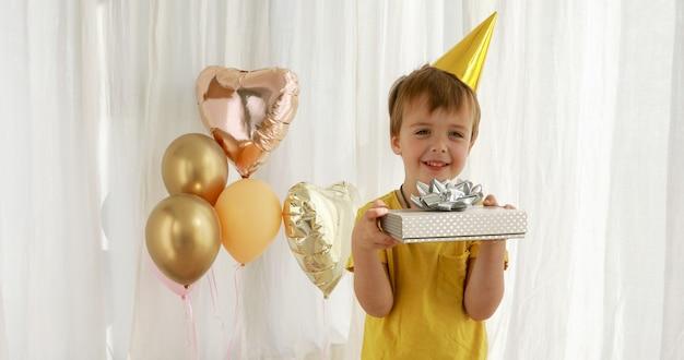 Il bambino divertente in maglietta gialla tiene il primo piano attuale della scatola di carta