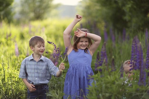 I bambini divertenti stanno ballando nell'erba nel parco