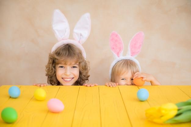 Bambini divertenti che indossano il coniglietto di pasqua. i bambini si divertono a casa