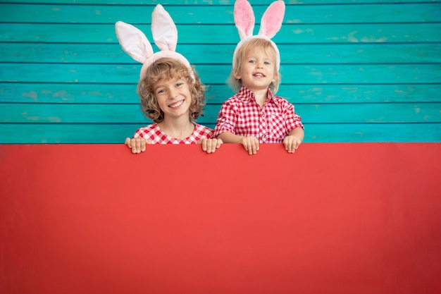 Bambini divertenti che indossano il coniglietto di pasqua. bambini che tengono scheda in bianco