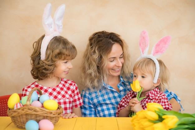 Bambini divertenti che indossano il coniglietto di pasqua. famiglia divertendosi a casa