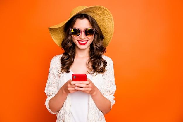 Divertente signora che tiene il telefono, mandare sms in vacanza, indossare un cappello da sole