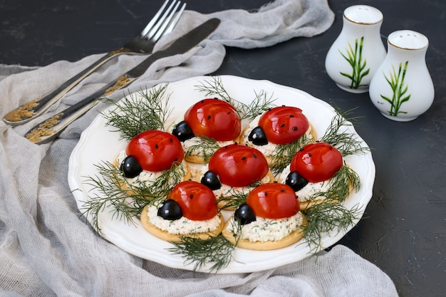 Antipasto a forma di spuntino divertente coccinella con pomodoro su cracker con formaggio su piatto bianco