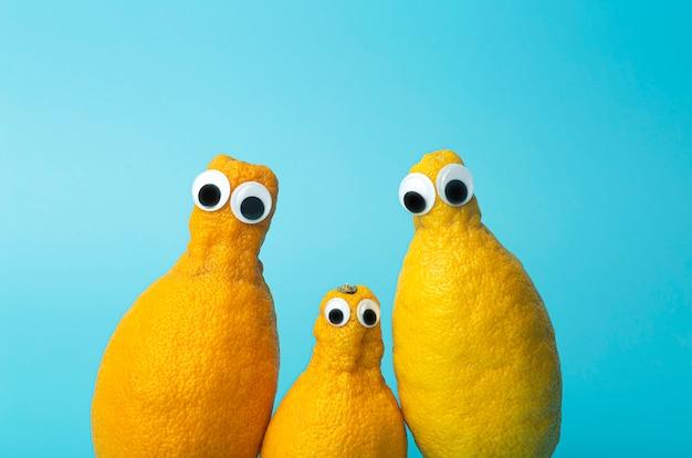 Limoni divertenti con gli occhi su sfondo blu. cibo brutto e brutto concetto di verdure, cibo per bambini (bambini), cibo faccia. cibo brutto e brutto concetto di verdure, cibo per bambini (bambini).