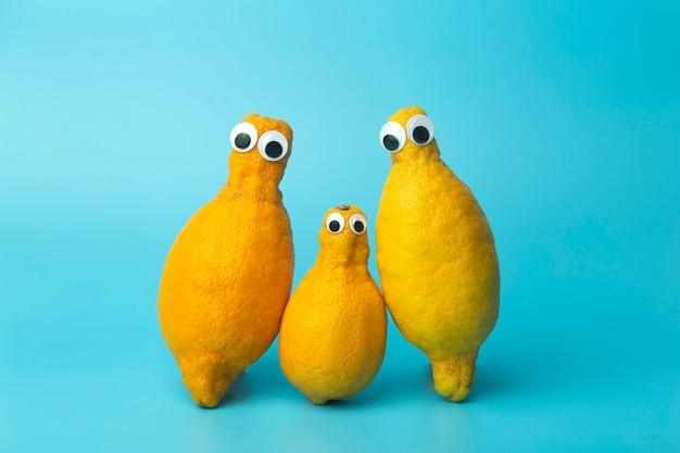Limoni divertenti con gli occhi su sfondo blu. cibo brutto e brutto concetto di verdure, cibo per bambini (bambini), cibo faccia.