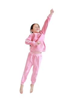 Piccolo bambino asiatico divertente in tuta da ginnastica rosa che salta in aria