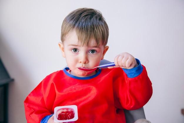 Ragazzino divertente che mangia gelatina rossa da un cucchiaio. stile di vita familiare e dietetico.