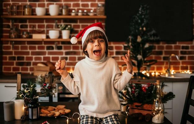 Un ragazzino divertente è seduto sul tavolo della cucina con un maglione bianco e un cappello rosso di natale con dei biscotti in mano
