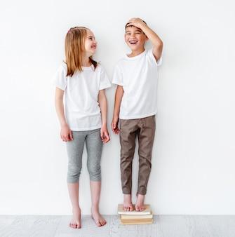 Ragazzino divertente che sta sui libri vicino alla sorella per essere più alto