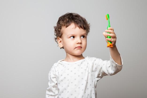Ragazzino divertente, bambino con uno spazzolino da denti in mano. uno sguardo serio al bancone. igiene al mattino e prima di coricarsi