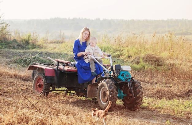 Ragazzino divertente con sua madre sul trattore con guida da terra in campo