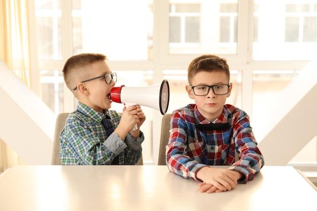 Ragazzino divertente con il megafono che grida al suo amico annoiato che si siede al tavolo