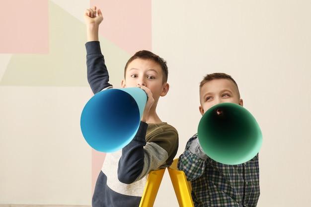 Ragazzini divertenti con megafoni di carta sul colore
