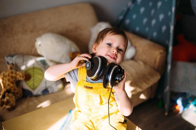 Piccolo bambino divertente che si diverte con le cuffie a casa ritratto